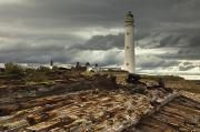 Dark Skies Posters - A Lighthouse And Piles Of Logs Poster by John Short