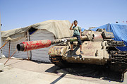 Muammar Gaddafi Posters - A T-55 Tank With Two Children Playing Poster by Andrew Chittock