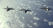 Warplane Prints - A Three-ship Formation Of F-22 Raptors Print by Stocktrek Images