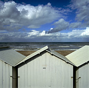 Wooden Building Posters - Beach huts under a stormy sky in Normandy Poster by Bernard Jaubert