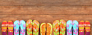 Footwear Framed Prints - Brightly colored flip-flops on wood  Framed Print by Sandra Cunningham