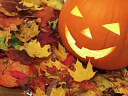 Carved Pumpkin On Fallen Leaves Print by Oleksiy Maksymenko