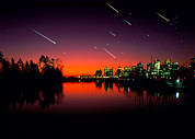 City At Night Posters - Composite Image Of Meteors Over A City At Night Poster by David Nunuk