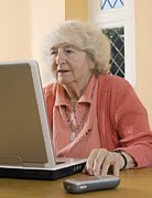 Laptop Posters - Elderly Woman Using A Laptop Computer Poster by Steve Horrell