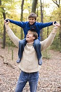 Child Care Posters - Father Carrying His Son In A Wood Poster by Ian Boddy