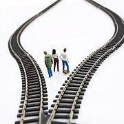 Contemplative Photos - Figurines between two tracks leading into different directions symbolic image for making decisions. by Bernard Jaubert