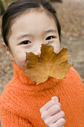 Shyness Prints - Girl Holding An Autumn Leaf Print by Ian Boddy