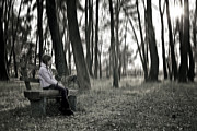 Sweater Posters - Girl sitting on a wooden bench in the forest against the light Poster by Joana Kruse