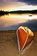 Setting Framed Prints - Lake sunset with canoe on beach Framed Print by Elena Elisseeva