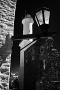 Lamp Post Prints - landmark lighthouse and old lamp post in Barrio Historico Colonia Del Sacramento Uruguay Print by Joe Fox