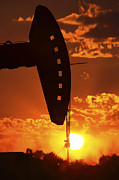 Saskatchewan Prairies Posters - Oil rig pump jack silhouetted by setting sun Poster by Mark Duffy