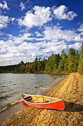 Pristine Prints - Red canoe on lake shore Print by Elena Elisseeva