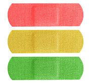 Illustrative Photo Prints - Red yellow and green bandaids Print by Blink Images