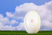 Sport Equipment Prints - Rugby ball teed up on grass Print by Richard Thomas
