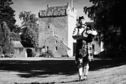 Bagpiper Framed Prints - scottish bagpipe player playing pipes in front of kilravock castle Scotland uk united kingdom Framed Print by Joe Fox