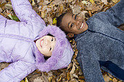 Multicultural Prints - Smiling Children Lying On Autumn Leaves Print by Ian Boddy