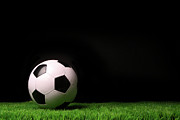 Game Photo Prints - Soccer ball on grass against black Print by Sandra Cunningham