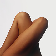 Womanly Posters - Top View Of The Tightly Crossed Legs Of A Woman Poster by Phil Jude