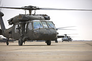 Taxiway Prints - Uh-60 Black Hawks Taxis Print by Terry Moore