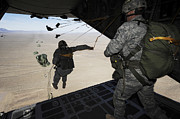 Paratrooper Photo Prints - U.s. Airmen Jump From A C-130 Hercules Print by Stocktrek Images