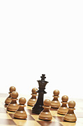 Chess Posters - White Pawns Surrounding Black Chess King Poster by Walter Zerla