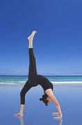 Wellbeing Prints - Woman doing yoga on the beach Print by Setsiri Silapasuwanchai
