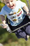 T-shirt Prints - Young Boy Smiling Swinging In A Swing Print by Robert Postma