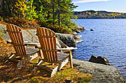 Fall Photos - Adirondack chairs at lake shore by Elena Elisseeva