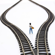 Figurines Framed Prints - Figurine between two tracks leading into different directions symbolic image for making decisions. Framed Print by Bernard Jaubert