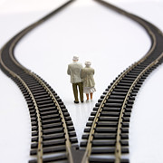 Figures Metal Prints - Figurines between two tracks leading into different directions symbolic image for making decisions. Metal Print by Bernard Jaubert
