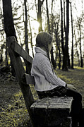 Girls Photos - Girl sitting on a wooden bench in the forest against the light by Joana Kruse