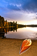 Autumn Trees Photo Prints - Lake sunset with canoe on beach Print by Elena Elisseeva