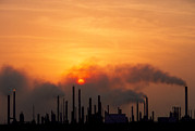 Oil Refinery Photo Posters - Smoking Chimneys Of An Oil Refinery At Sunset Poster by David Nunuk