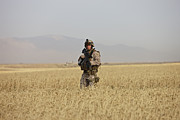 Foot Patrol Photos - U.s. Marine Patrols A Wadi Near Kunduz by Terry Moore