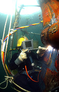 Swimsuit Photography Prints - U.s. Navy Diver Welds A Repair Patch Print by Stocktrek Images