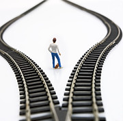 Figures Metal Prints - Figurine between two tracks leading into different directions symbolic image for making decisions. Metal Print by Bernard Jaubert