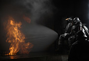 Protective Fire Framed Prints - Firefighters Extinguish A Simulated Framed Print by Stocktrek Images
