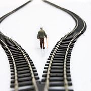 Male Likeness Metal Prints - Figurine between two tracks leading into different directions symbolic image for making decisions. Metal Print by Bernard Jaubert