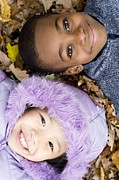 Two By Two Framed Prints - Smiling Children Lying On Autumn Leaves Framed Print by Ian Boddy