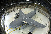 Hangar Framed Prints - A C-17 Globemaster Iii Sits In Hangar 4 Framed Print by Stocktrek Images