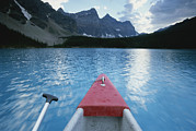 Alberta Rocky Mountains Prints - A Canoe Glides Across Moraine Lake Print by Bill Hatcher