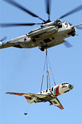 Hu Posters - A Ch-53 Sea Stallion Lifts A Hu-25 Poster by Stocktrek Images