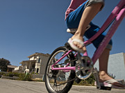 Two Wheeler Photo Prints - A Child Rides Her Bike Along The Beach Print by Stacy Gold