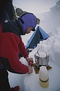Stoves Framed Prints - A Climber Cooks At A Snowy Camp High Framed Print by Gordon Wiltsie