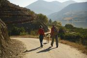 Dirt Roads Photos - A Couple With Their Dog Hiking by Michael Melford