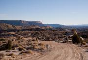 Dirt Roads Photos - A Dirt Road Leads Past Cliffs And Mesas by Taylor S. Kennedy