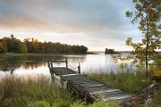 Calm Waters Photo Prints - A Dock On A Lake At Sunrise Near Wawa Print by Susan Dykstra