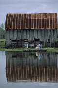 Agricultural Structures Posters - A Family Travels By Rowboat Poster by Joel Sartore