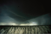 Tornadoes Photo Posters - A Heavy Dark Cloud Hangs Over A Flat Poster by Carsten Peter