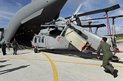 Military Base Posters - A Helicopter Is Loaded Onto A C-17 Poster by Stocktrek Images